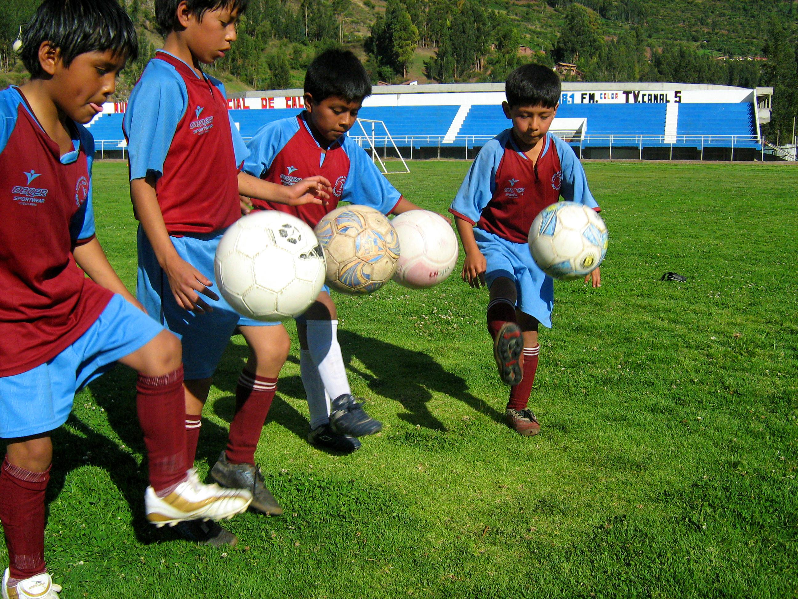 A Projects Abroad volunteer teaching sports in Peru shows children a football kicking technique